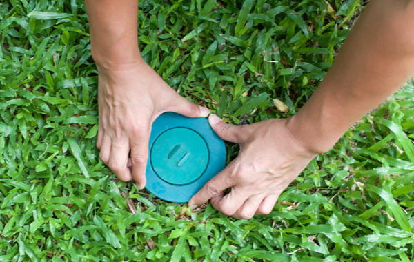 a person installing a termite bait station into the ground using both hands
